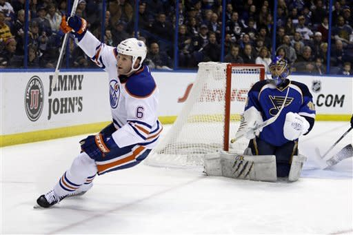 Edmonton Oilers' Ryan Whitney, left, celebrates after scoring past St. Louis Blues goalie Jaroslav Halak, of Slovakia, during the first period of an NHL hockey game Friday, March 1, 2013, in St. Louis. (AP Photo/Jeff Roberson)