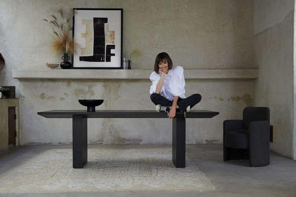 PHOTO: Leanne Ford sitting on a dining table from her collection with Crate and Barrel. (Crate and Barrel)