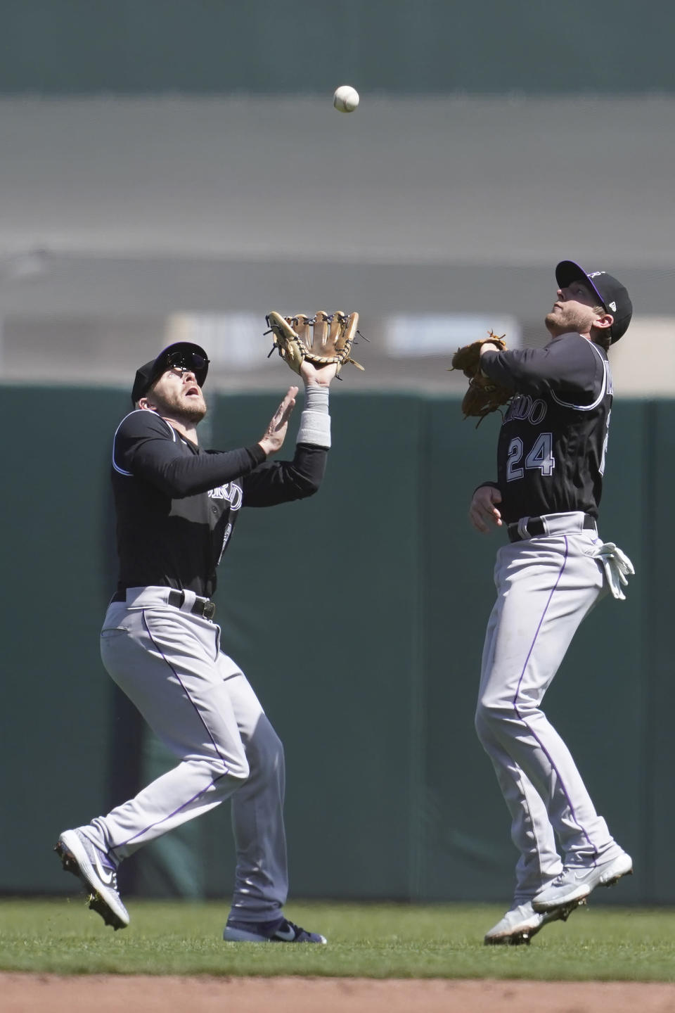 Colorado Rockies shortstop Trevor Story, left, catches a fly ball hit by San Francisco Giants' Brandon Crawford next to second baseman Ryan McMahon (24) during the second inning of a baseball game in San Francisco, Saturday, April 10, 2021. (AP Photo/Jeff Chiu)