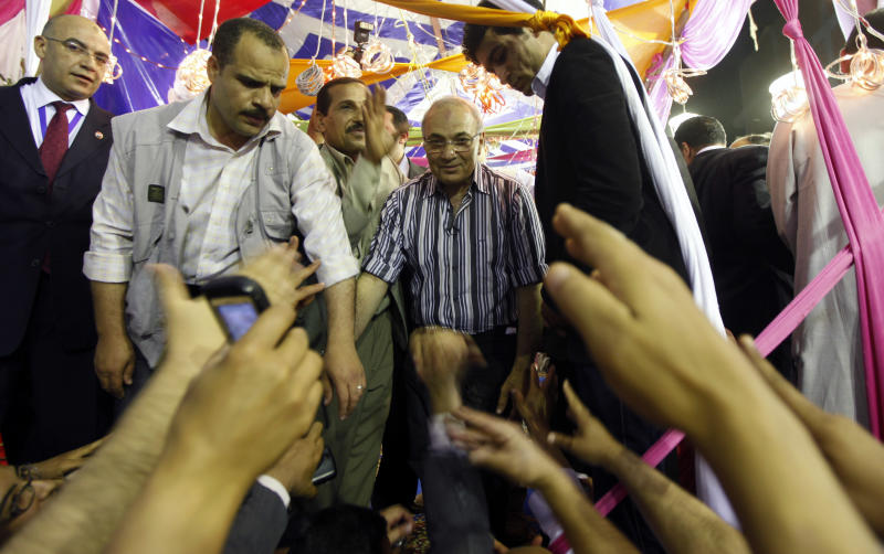 Egyptian presidential candidate for the upcoming elections Ahmed Shafiq, center, is welcomed by his supporters during a meeting in Tanta, about 90 km (56 miles) north of Cairo, Egypt, Friday, May 11, 2012.(AP Photo/Khalil Hamra)