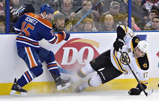 Boston Bruins' Milan Lucic (17) is checked by Edmonton Oilers' Nick Schultz (15) during the first period of an NHL hockey game, Thursday, Dec. 12, 2013 in Edmonton, Alberta. (AP Photo/The Canadian Press, Jason Franson)