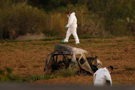 Forensic experts walk in a field after a powerful bomb blew up a car (Foreground) and killed investigative journalist Daphne Caruana Galizia in Bidnija, Malta, October 16, 2017. REUTERS/Darrin Zammit Lupi
