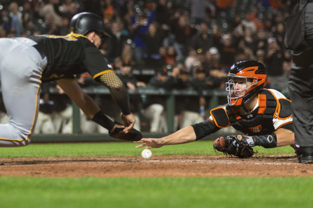 San Francisco Giants catcher Buster Posey, right, loses possession of the ball as Pittsburgh Pirates' Kevin Newman, left, scrambles safely back to home plate in the ninth inning of a baseball game in San Francisco, Monday, Sept. 9, 2019. (AP Photo/John Hefti)