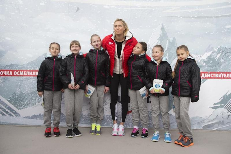 Russian tennis player Maria Sharapova poses with children while visiting her first court of Kafelnikov Tennis School in Riviera Park in Sochi, Russia, Wednesday, Feb. 5, 2014, prior to the start of the 2014 Winter Olympics. (AP Photo/Pavel Golovkin)
