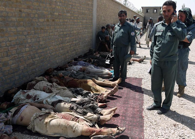 Afghan policemen are seen near bodies of Taliban fighters at a police station after an operation in Qala-e Zal district of Kunduz province, northern Afghanistan, Saturday, June 22, 2013. Taliban militants attacked local security checkpoints in the provincial capital in northern Afghanistan, Afghan officials said Saturday. (AP Photo/Ahmad Yama)