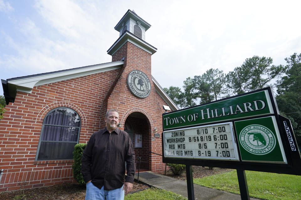 Town Councilman Kenny Sims in front of the city hall of Hilliard, Fla.,Tuesday, Aug. 10, 2021. Sims has been vaccinated but cannot convince his mother, Frances Sims, to get the shot. (AP Photo/John Raoux)