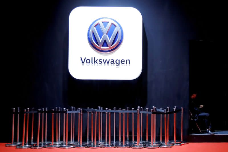 FILE PHOTO: Man uses phone under VW logo at the auto show in Shanghai