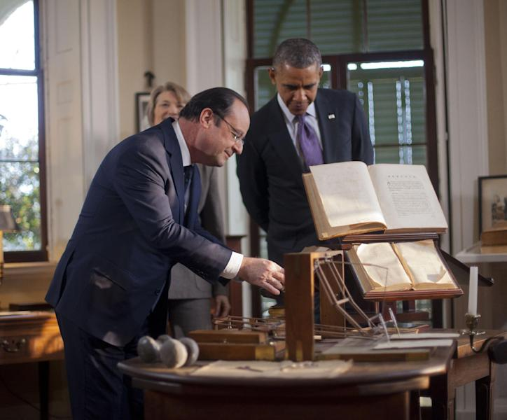 President Barack Obama, right, watches as French President Francois Hollande, left, looks over items on on the desk during a tour of Thomas Jefferson's office at Monticello, Monday, Feb. 10, 2014, in Charlottesville, Va. Leading the tour is Leslie Bowman, president of the Thomas Jefferson Foundation. (AP Photo/Pablo Martinez Monsivais)