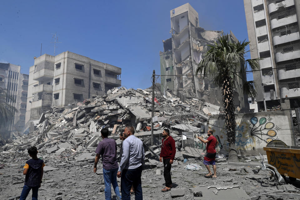 People insect the the rubble of the Yazegi residential building that was destroyed by an Israeli airstrike, in Gaza City, Sunday, May 16, 2021. The 57-member Organization of Islamic Cooperation held an emergency virtual meeting Sunday over the situation in Gaza calling for an end to Israel's military attacks on the Gaza Strip. (AP Photo/Adel Hana)