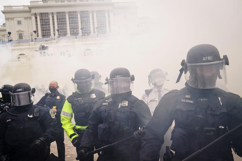 Supporters loyal to President Donald Trump clash with authorities before successfully breaching the Capitol building during a riot on the grounds, on Jan. 6, 2021.