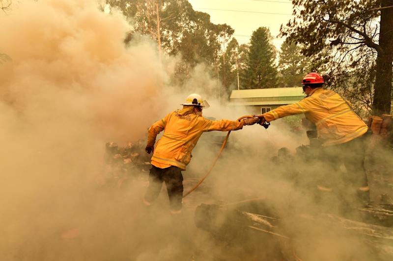 Firefighters hose down a burning woodpile during a bushfire in Werombi, 50km southwest of Sydney