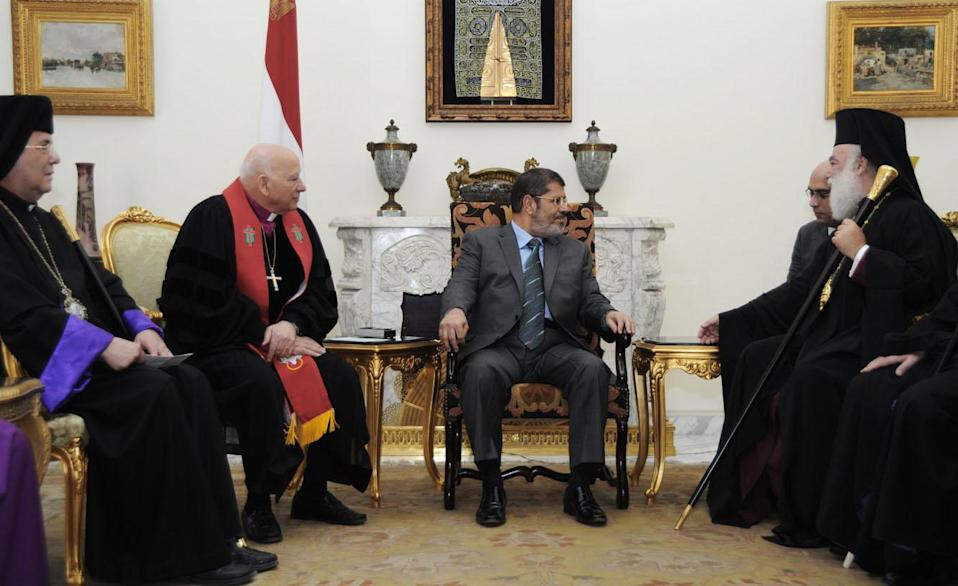 In this photo released by Middle East News Agency, the Egyptian official news agency, President-elect Mohammed Morsi, center, meets with Christian leaders, names not given, in Cairo, Egypt, Monday, June 27, 2012. Now that Egypt has its first freely elected civilian president, the still-dominant military may be seeking to emulate the Turkish model a mostly Muslim nation with a history of military rule and democratic evolution. (AP Photo/Mohammed Abd El-Maaty, Middle East News Agency, HO)