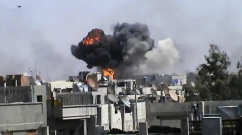 In this image made from amateur video released by the Shaam News Network and accessed Wednesday, April 18, 2012, smoke billows an impact following purported shelling in Khaldiyeh district, Homs, Syria. Nearly a week after a cease-fire took effect, Syrian troops pounded a rebel stronghold Wednesday as the country's foreign minister met with his Chinese counterpart in Beijing during the latest round of talks aimed at preventing the truce from unraveling. (AP Photo/Shaam News Network via AP video) TV OUT, THE ASSOCIATED PRESS CANNOT INDEPENDENTLY VERIFY THE CONTENT, DATE, LOCATION OR AUTHENTICITY OF THIS MATERIAL