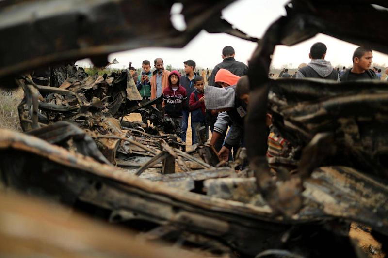 Palestinians gather around the remains of a vehicle that was destroyed in an Israeli air strike, in Khan Younis in the southern Gaza Strip (REUTERS/Suhaib Salem)