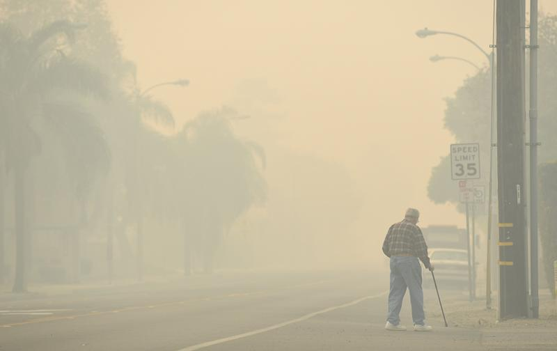 A man walks along a road as the Thomas fire leaves smoke in Ventura.