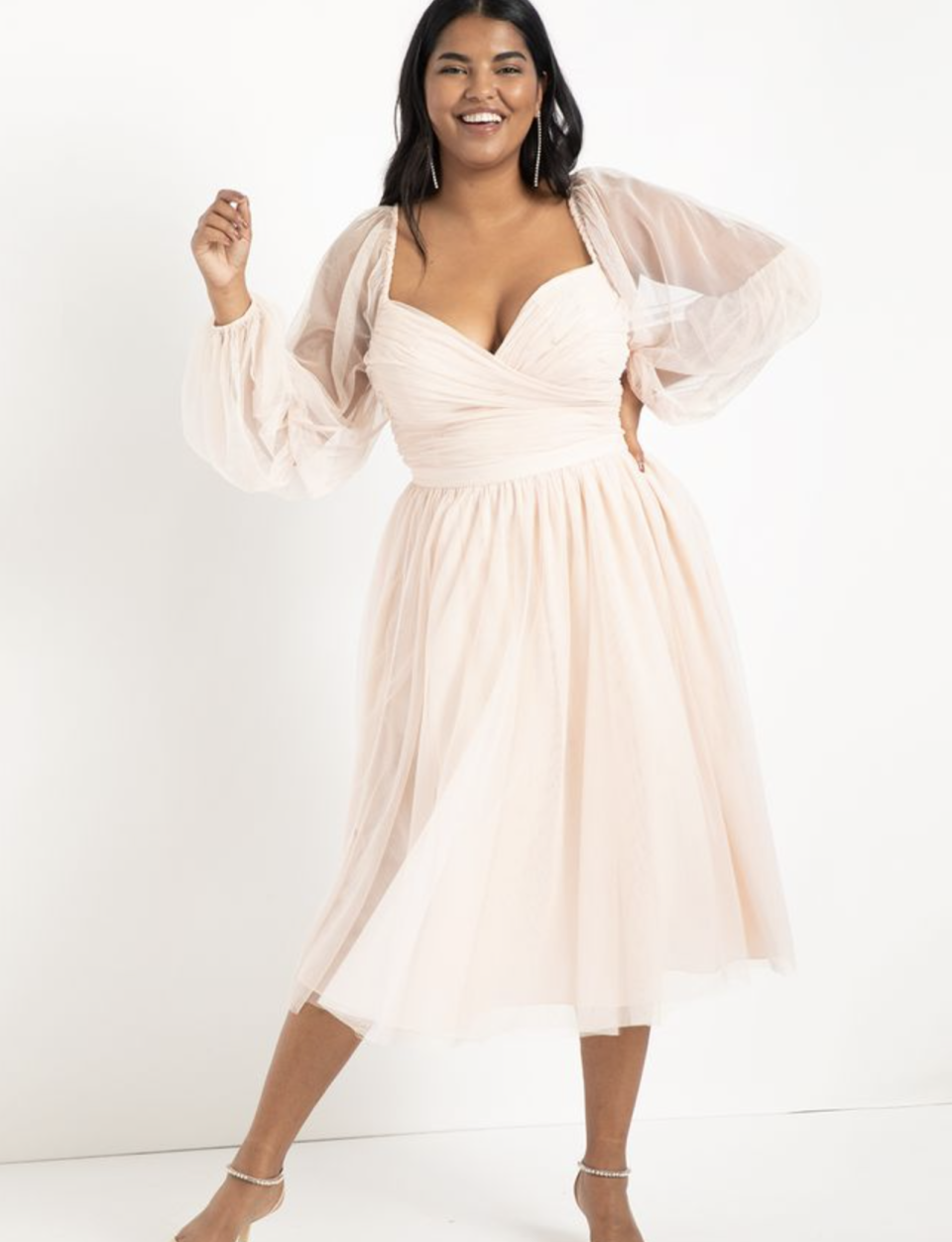 plus size model posing in  blush pink midi dress with sheer long sleeves