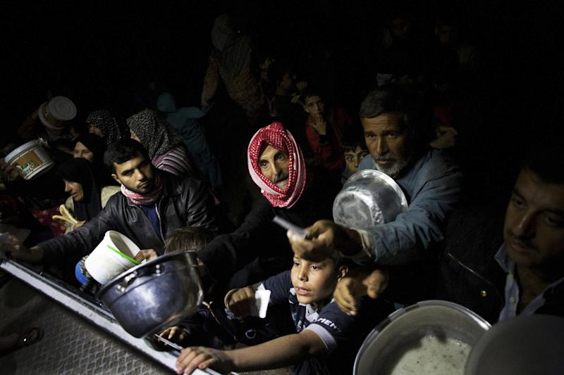 FILE - Displaced Syrian men wait for food near an NGO charitable kitchen in a refugee camp near Azaz, Syria, Oct. 23, 2012. This image was one in a series of 20 by AP photographers that won the 2013 Pulitzer Prize in Breaking News Photography. (AP Photo/Manu Brabo, File)