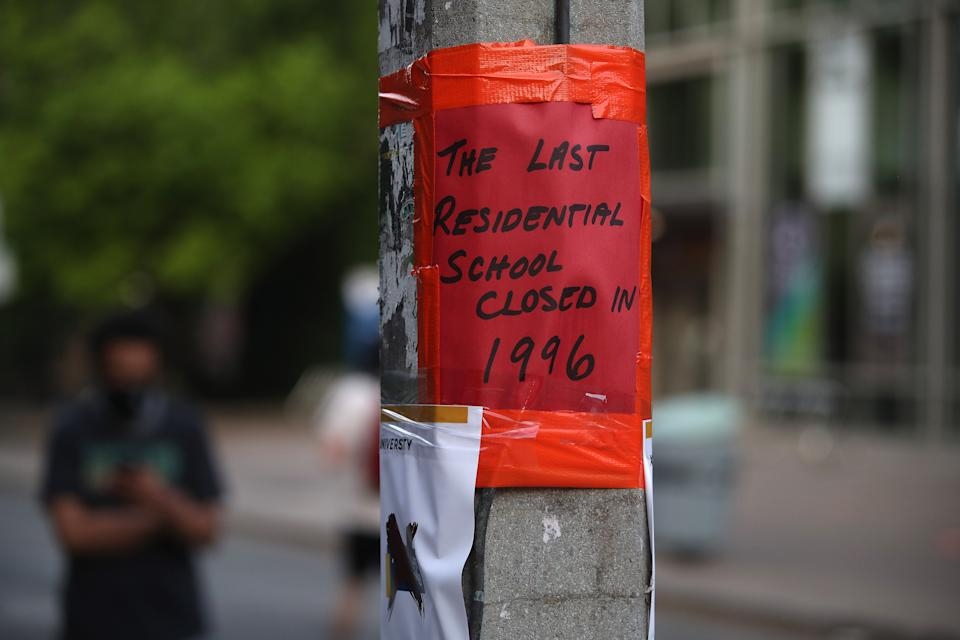 """<p>A sign in downtown Toronto reads: """"The last residential school closed in 1996."""" (Steve Russell/Toronto Star via Getty Images)</p>"""