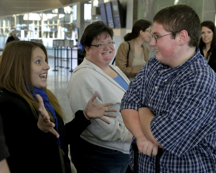 Sixteen-year-old Jason Alexander, right, talks with his sister Katie, left, and mother, Debbie, Friday, Dec. 21, 2012, at the Kansas City International Airport in Kansas City, Mo., after returning from a four-month stay at a weight-loss boarding school. Alexander, nearly 100 pounds lighter, was among 14 students from the Independence, Mo., school district to attend the program, losing 756 pounds among themselves. (AP Photo/Charlie Riedel)