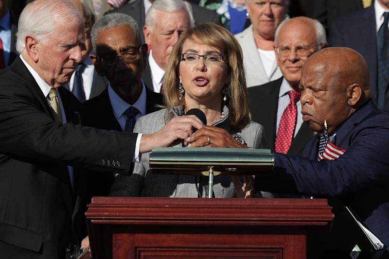 <strong>Gabby Giffords, who was serving in Congress when she was shot in 2011, addresses a rally with fellow Democrats after the Las Vegas mass shooting, calling for legislation to strengthen background checks</strong> (Chip Somodevilla via Getty Images)