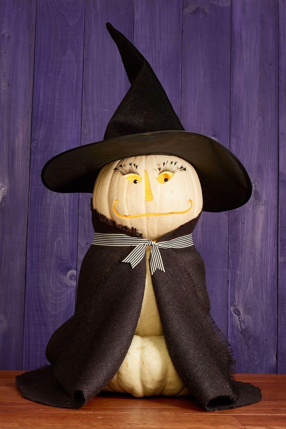 "<p>Sweet and friendly with lush eyelashes that'll make anyone jealous this witch pumpkin is ready to great trick-or treaters with a smile!</p><p><strong>Make the pumpkin: </strong>Stack three white pumpkins. Carve a friendly face in the top most pumpkin. Paint on eyelashes with black acrylic paint and use pushpins to create pupils. Wrap a piece of black felt around the ""neck"" and tie in place with ribbon. Top it all off with a witch hat.</p><p><a class=""link rapid-noclick-resp"" href=""https://www.amazon.com/Acrylic-Felt-Yard-Wide-Long/dp/B001P22TIS/ref=sr_1_3?tag=syn-yahoo-20&ascsubtag=%5Bartid%7C10050.g.279%5Bsrc%7Cyahoo-us"" rel=""nofollow noopener"" target=""_blank"" data-ylk=""slk:SHOP BLACK FELT"">SHOP BLACK FELT</a></p>"