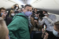 FILE - In this Jan. 17, 2021, file photo, Alexei Navalny is surrounded by journalists in a plane before a flight to Moscow in the Berlin Brandenburg Airport. Rattled by nationwide protests over Navalny, Russian authorities are moving rapidly to block any new ones – from putting legal pressure on his allies to launching a campaign to discredit the demonstrations. (AP Photo/Mstyslav Chernov, File)