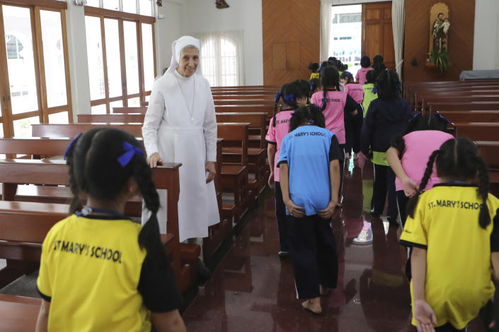 In this Aug. 27, 2019, photo, ST. Mary's School Vice Principal Sister Ana Rosa Sivori, second left, watches as students leave a church at the girls' school in Udon Thani, about 570 kilometers (355 miles) northeast of Bangkok, Thailand. Sister Ana Rosa Sivori, originally from Buenos Aires in Argentina, shares a great-grandfather with Jorge Mario Bergoglio, who, six years ago, became Pope Francis. So, she and the pontiff are second cousins. (AP Photo/Sakchai Lalit)