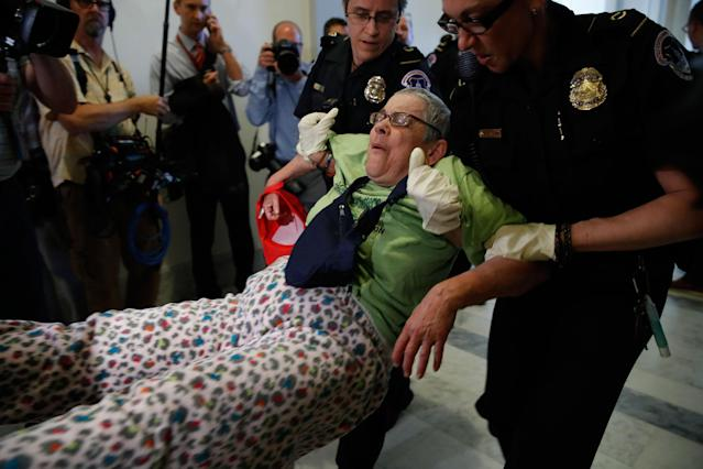 <p>People are removed from a sit-in outside of Senate Majority Leader Mitch McConnell's office as they protest proposed cuts to Medicaid, Thursday, June 22, 2017 on Capitol Hill in Washington. (Photo: Jacquelyn Martin/AP) </p>
