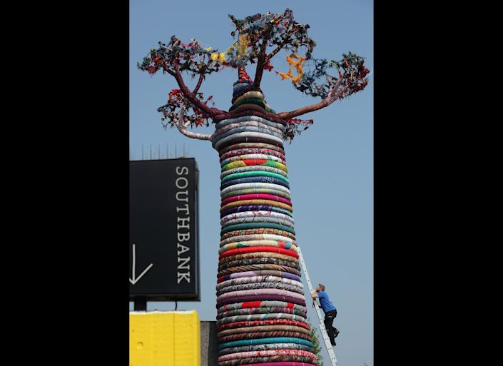 Mike De Butts adds the finishing touches to a giant Baobab Tree sculpture entitled 'Under the Baobab', outside the Southbank Centre on May 24, 2012 in London, England. The Pirate Technics' installation is made from a selection of brightly coloured fabrics from around the world, and is part of the Southbank Centre's 'Festival of the World' exhibition, which includes a series of large scale pieces of art that will be in place around the Southbank centre over the Summer.