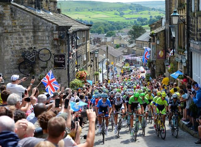 Crowds line the streets of Haworth, West Yorkshire to cheer on the Tour de France peloton during its route from York to Sheffield. Yorkshire hosted the opening two stages of the annual race in 2014, which was won by Italian rider Vincenzo Nibali (Martin Rickett/PA)