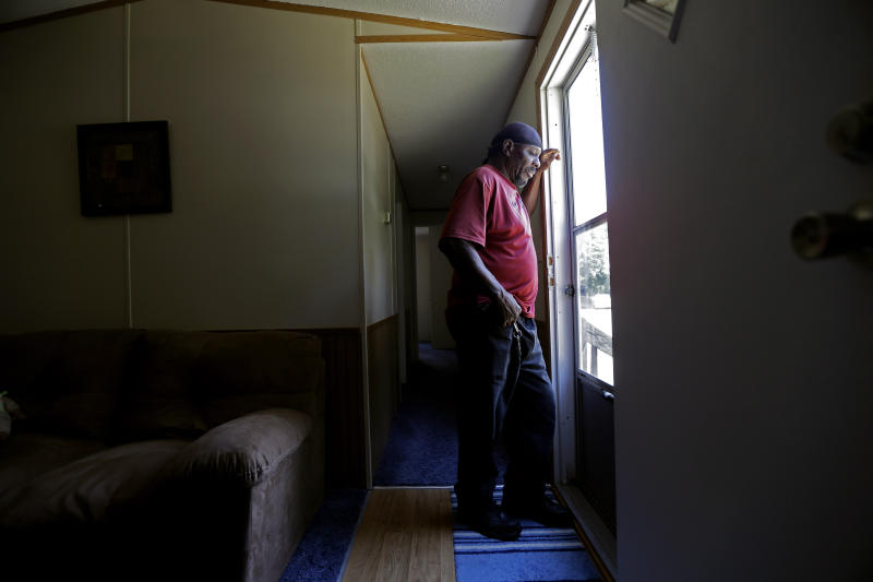In this photo taken Wednesday, May 29, 2019, resident James Lesane stands at the entrance to his mobile home in Lumberton, N.C. Every month, Lesane pays what he can afford for his mobile home lot rental; $150. But, after the Florida-based company Time Out Communities bought the park, he got a notice in the beginning of this year that his lot rent would be increasing to $465 a month. Mobile home residents in Robeson County, North Carolina are seeing increasing rent prices after being slammed by hurricanes Matthew and Florence.(AP Photo/Gerry Broome)