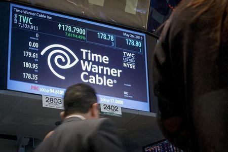 Traders work at the post where Time Warner Cable is traded on the floor of the New York Stock Exchange