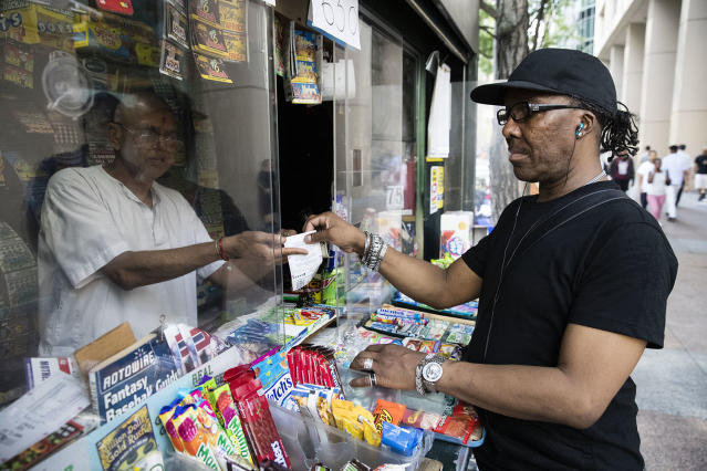 <p>Atul Amin, left, sells a customer a Powerball ticket at his news stand in Philadelphia, Aug. 22, 2017. The Powerball jackpot has climbed to $700 million, giving players a chance to dream of winning the second-largest lottery prize in U.S. history. (AP Photo/Matt Rourke) </p>