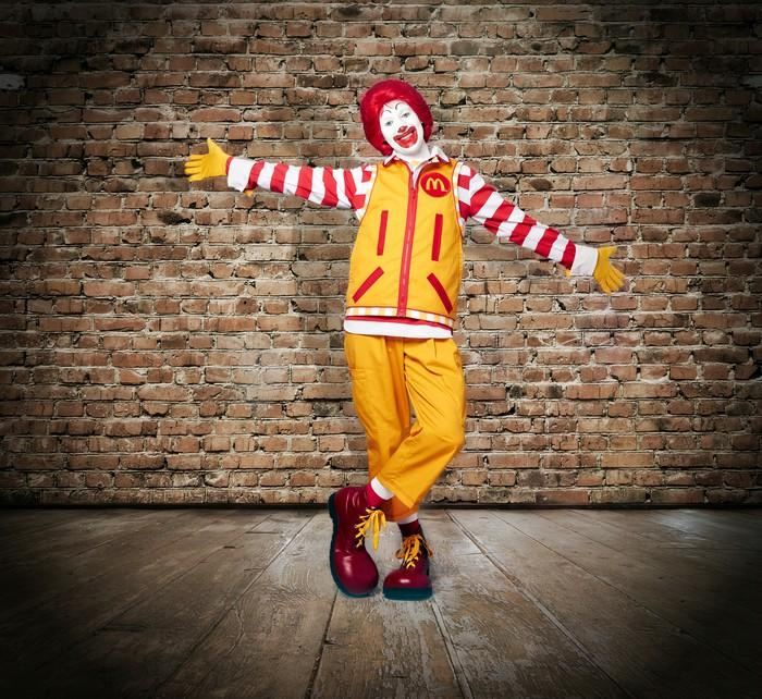 A costumed Ronald McDonald in front of a brick wall.