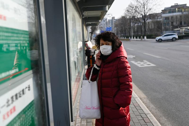 A woman wearing a mask uses a mobile phone while waiting for a bus in Beijing on January 21, 2020. - The number of people in China infected by a new SARS-like virus jumped to 291 on January 21, according to authorities. (Photo by WANG Zhao / AFP) (Photo by WANG ZHAO/AFP via Getty Images)