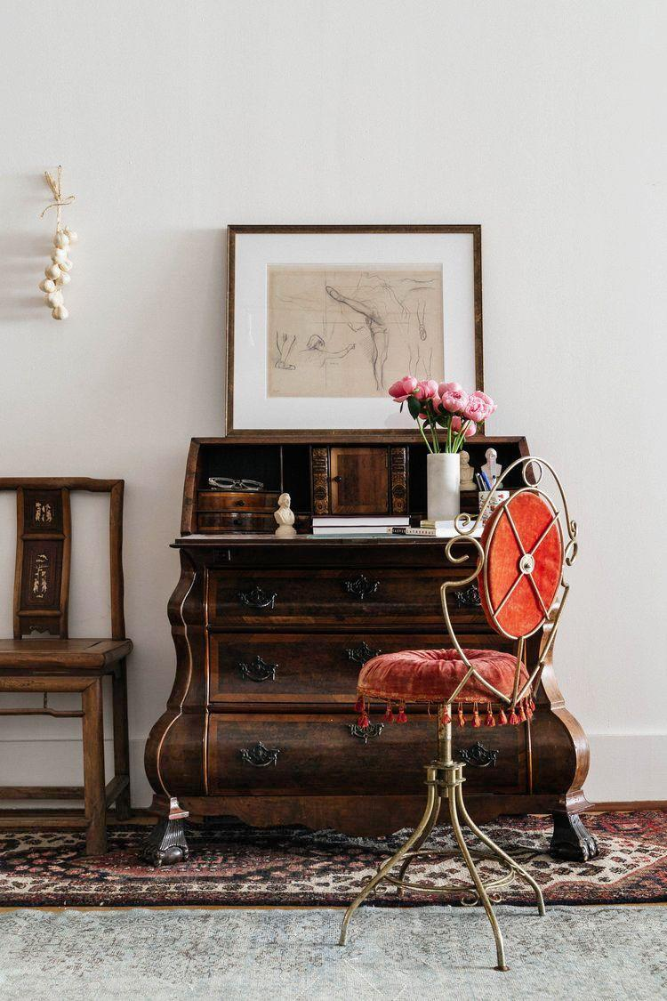 """<p>Investing in a proper desk is a great place to start, but if space is an issue, don't corner yourself into buying a piece of furniture with only one purpose. An antique secretary with a drop-down writing surface, like this piece in a workspace by <a href=""""https://www.jaejoodesigns.com/"""" rel=""""nofollow noopener"""" target=""""_blank"""" data-ylk=""""slk:Jae Joo Design"""" class=""""link rapid-noclick-resp"""">Jae Joo Design</a>, has plenty of drawers and shelves to hide paperwork and other essentials but takes up way less space than a traditional desk when not in use.</p>"""