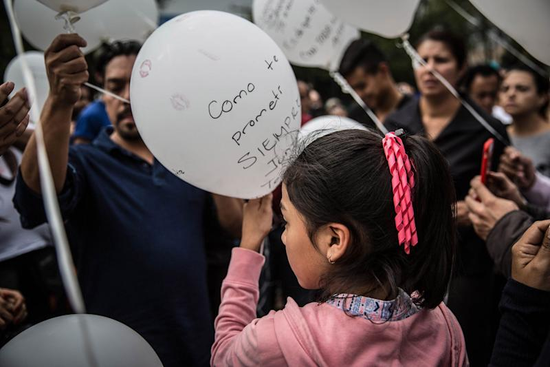 People write the names of victims and messages for them on balloons.