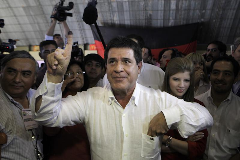 Paraguay's Colorado Party's Presidential candidate Horacio Cartes shows his inked finger which was marked after casting his ballot during general elections in Asuncion, Paraguay, Sunday, April 21, 2013. Most polls indicate that tobacco magnate and soccer executive Horacio Cartes of the Colorado Part will win the presidency handily over his chief rival, Sen. Efrain Alegre of  Liberal Party. (AP Photo/Jorge Saenz)