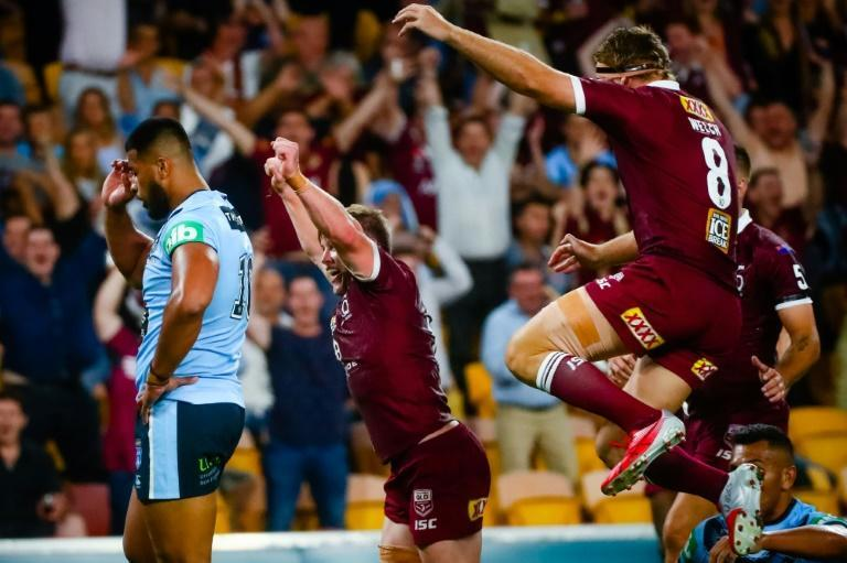 Queensland's Harry Grant (C) celebrates a try in front of capacity crowd
