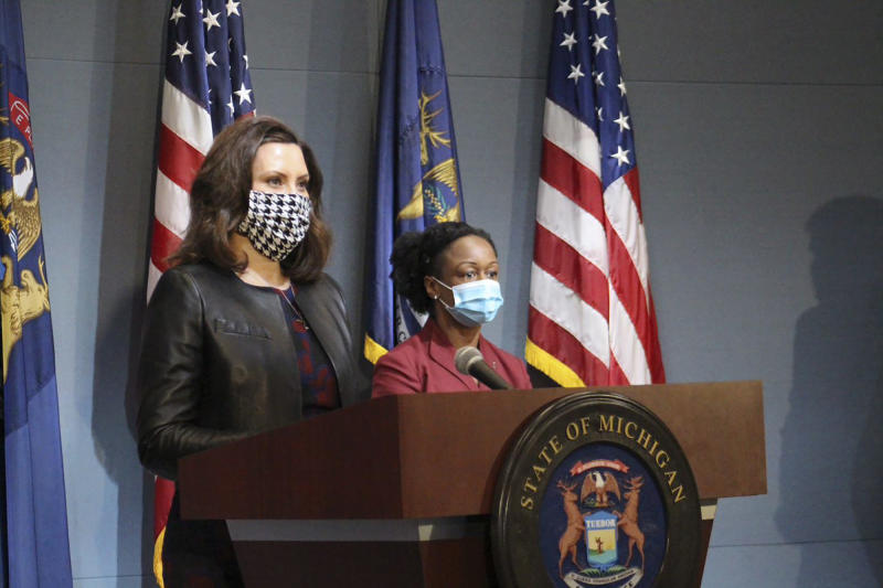 Michigan Gov. Gretchen Whitmer, wearing a mask, addresses the state during a speech