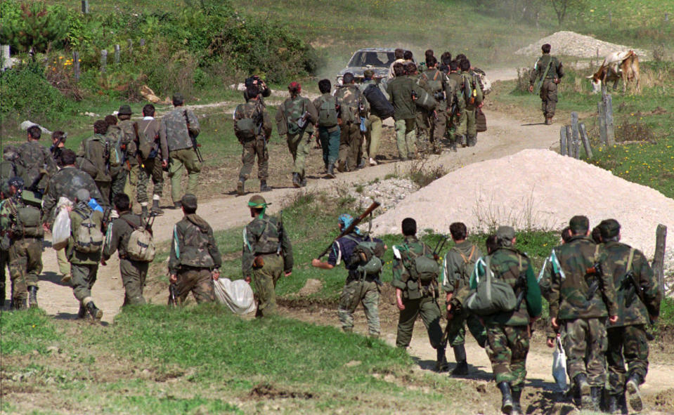 FILE - In this Sept. 28, 1995. file photo, a line of Bosnian government troops makes its way to the front-line near Mrkonjic Grad 120kms (80mls) north west of Sarajevo, Bosnia. While it brought an end to the fighting, the Dayton peace agreement baked in the ethnic divisions, establishing a complicated and fragmented state structure with two semi-autonomous entities, Serb-run Republika Srpska and a Federation shared by Bosniak and Croats, linked by weak joint institutions. (AP Photo/Darko Bandic, File)