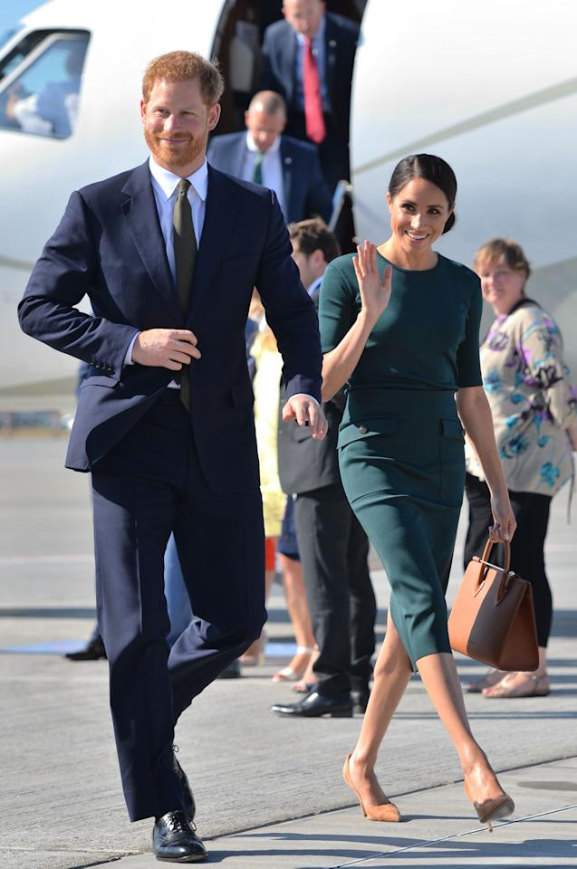 <p>For the Duke and Duchess of Sussex's first overseas engagement as newlyweds to Dublin, Meghan dressed diplomatically in a £1,105 forest green skirt by Givenchy. She accessorised the look with a £475 Strathberry midi tote.<em> [Photo: PA]</em> </p>