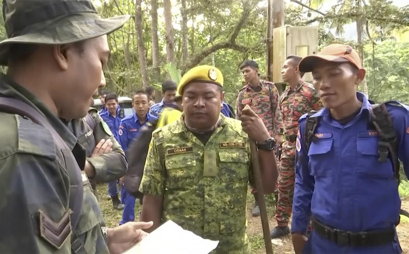 In this image from a video, rescuers brief as they conduct a search and rescue operation for a missing British girl at a forest in Seremban, Malaysia Tuesday, Aug. 13, 2019. Malaysian police say rescuers have found the body of a Caucasian female in the forest surrounding a nature resort where a 15-year-old London girl was reported missing more than a week ago. State police chief says officials are in the process of determining whether the body, which was found on Tuesday, is Nora Anne Quoirin. (AP Photo)