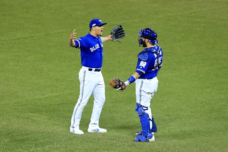 Roberto Osuna #54 and Russell Martin #55 of the Toronto Blue Jays celebrate after defeating the Cleveland Indians with a score of 5 to 1 in game four of the American League Championship Series at Rogers Centre on October 18, 2016 in Toronto, Canada