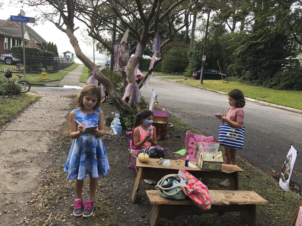 Maya Gebler, center, Cate and Sophie Carroll , right, write letters to fairies in Norfolk, Virginia on Monday Oct. 12, 2020. In the last few months, more than 700 letters have arrived at a fairy tree village outside the home of a journalist and children's book author. (AP Photo/Ben Finley).