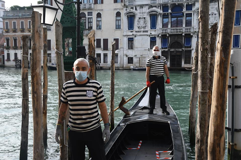 Gondoliers wearing a face mask stand on a gondola on a Venice canal as they resume their service on May 18, 2020 during the country's lockdown aimed at curbing the spread of the COVID-19 infection, caused by the novel coronavirus. - Restaurants and churches reopen in Italy on May 18, 2020 as part of a fresh wave of lockdown easing in Europe and the country's latest step in a cautious, gradual return to normality, allowing businesses and churches to reopen after a two-month lockdown. (Photo by ANDREA PATTARO / AFP) (Photo by ANDREA PATTARO/AFP via Getty Images)