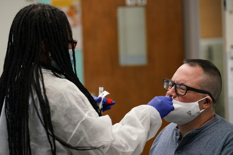 """Instructor Frank Esposito submits to a COVID-19 nasal swab test at West Brooklyn Community High School, Thursday, Oct. 29, 2020, in New York. The high school is a """"transfer school,"""" catering to a students who haven't done well elsewhere, giving them a chance to graduate and succeed. The school reopened Monday after it was forced to shut down for three weeks due to a coronavirus outbreak in the immediate neighborhood. (AP Photo/Kathy Willens)"""