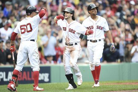 Oct 9, 2017; Boston, MA, USA; Boston Red Sox left fielder Andrew Benintendi (center) is congratulated by right fielder Mookie Betts (50) for hitting a two-run home run against the Houston Astros during the fifth inning in game four of the 2017 ALDS playoff baseball series at Fenway Park. Mandatory Credit: Bob DeChiara-USA TODAY Sports