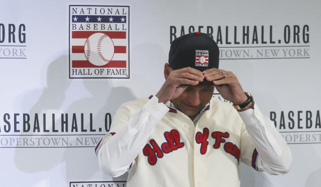 New York Yankees shortstop Derek Jeter fits his cap after receiving his outfit for the Baseball Hall of Fame, Wednesday Jan. 22, 2020, during a news conference in New York. Jeter and Colorado Rockies outfielder Larry Walker will both join the 2020 Hall of Fame class. (AP Photo/Bebeto Matthews)