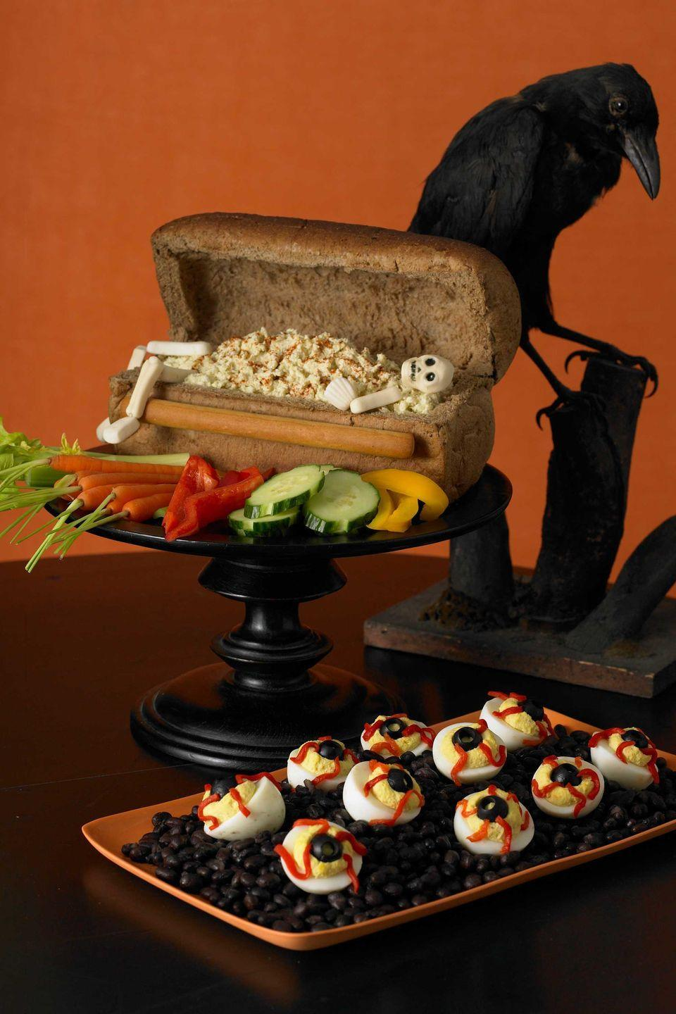 """<p>Whip up a batch of creamy deviled eggs and then turn them into eerie-looking """"eyeballs"""" with a few simple additions: black olive slices for the pupils and thinly sliced pimiento for veins.<br></p><p><a href=""""https://www.womansday.com/food-recipes/food-drinks/recipes/a10067/bloodshot-deviled-eyeballs-recipe-121384/"""" rel=""""nofollow noopener"""" target=""""_blank"""" data-ylk=""""slk:Get the Bloodshot Deviled Eyeballs recipe."""" class=""""link rapid-noclick-resp""""><em>Get the Bloodshot Deviled Eyeballs recipe.</em></a></p>"""